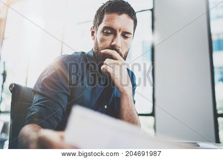 Young bearded man working at sunny loft office on laptop.Businessman holding paper documents hand .Blurred background, horizontal