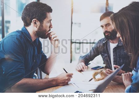 Young business people discussing new project in modern office.Group of three coworkers making conversations at meeting room.Horizontal, blurred background