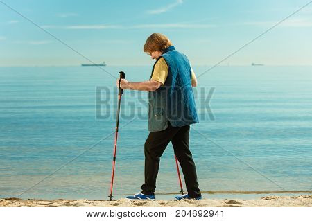 Healthy lifestyle in old age. Senior woman practicing nordic walking on sandy beach Active elderly female enjoying warm sunny day.