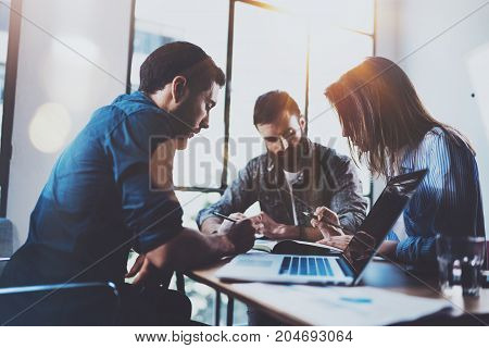 Teamwork brainstorming process.Young man working together with partners in modern office loft.Business startup concept.Blurred background.Flares.Cropped