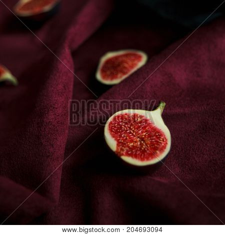 Cut Fresh Figs Lying On Burgundy Velvet.