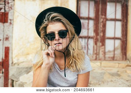 Cocky and confident femme fatale woman with dark vintage sunglasses and cowboy hat eats or chews lollipop stick in front of wild west style house