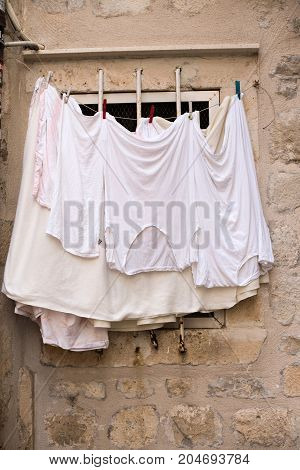 Fresh white clothes after wash and laundry hang dry on window shelf of old cobbled brick building in mediterranean european town or village country life