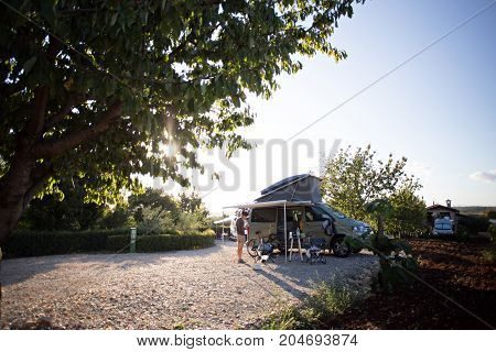 Young tourist explorer stands next to camping van in beautiful french provence vineyard on sunset evening concept vacation nomad life of adventure