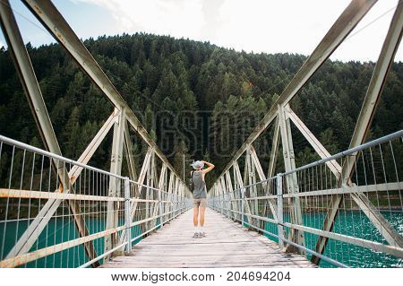 Young fit adventurer man with camera makes photo of nature stands in middle of metal pedestrian bridge over pristine blue water lake that connects two shores forest and city