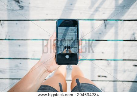 Young social media influencer with marketing ideas makes photo on smartphone of sneaker or running shoes of famous brand standing on wooden bridge floor