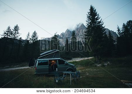 Small travel vehicle camping van or big car with folding rooftop with bed is parked on secluded wild site under huge mountain formation in dolomites surrounded by forest