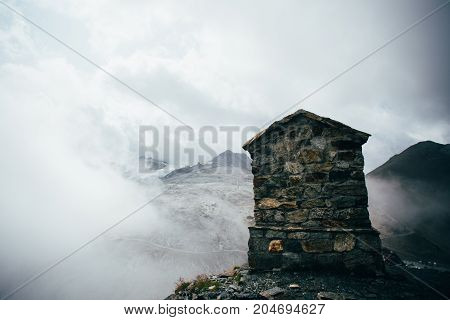 Structure made of stone and bricks to commemorate or signal top of summit on mountain covered with clouds alps or dolomites exploration and hiking guide