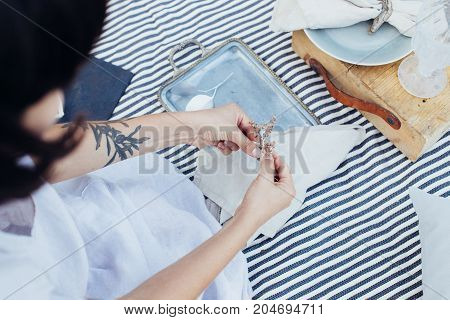 Close up soft focus shot of female decorator or florist preparing decorations for setting up picnic or restaurant dinner table with napkin ceramic vintage plates and flowers