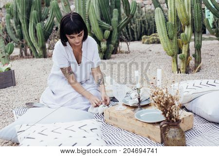Woman decorator designer or florist sets up location for romantic surprise date or wedding engagement proposal in park with chic and bohemian atmosphere
