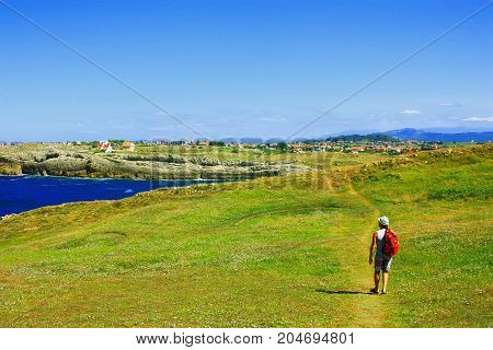 Tourist man walking on a green hill trail with the red blackpack