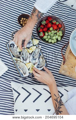 Unconventional hipster couple enjoys luxurious snack of fresh oysters during romantic date on picnic blanket in chic and dreamy setting with fruits and olives