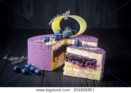 Delicious lavender cake with blueberries on black wooden table