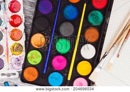 Sets Of Watercolors And Different Paintbrushes On The Gray Wooden Background