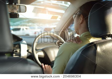 Rear view of Asian glasses business woman having pain on her shoulder back and neck while driving a car. Illness exhausted disease tired for overtime working concept.