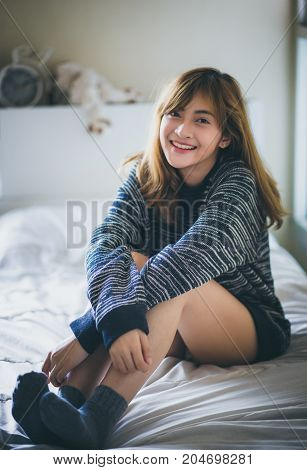 Close up of attractive girl smiling while sitting on a bed in the winter and look to the camera.