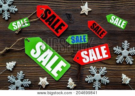 Christmas sale. Sale labels near xmas decor on wooden background top view.