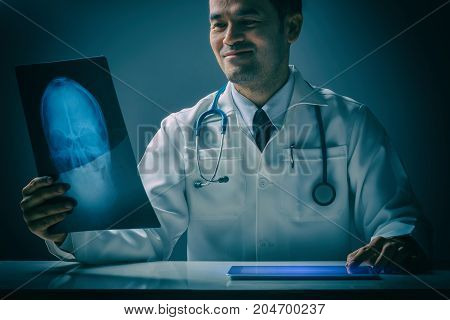 Asian male doctor looking at X-Ray radiography He has stethoscope and tablet still life style concept consulting treat patients.