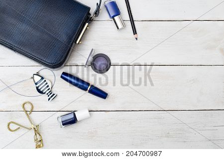 Feminine accessories. Dark blue handbag and blue make up