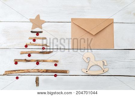 A wooden Christmas tree with berries of a viburnum and an envelope on a white wooden background. Mock up