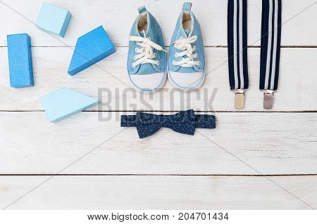 Suspenders a bow tie and blue shoes for a boy. view from above
