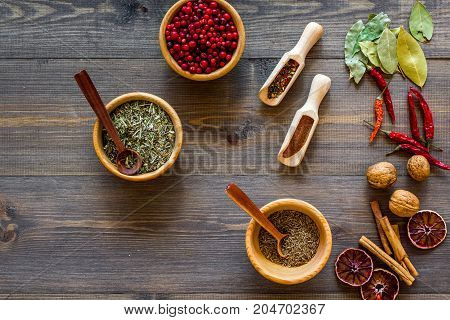 Colorful dry herbs and spices for cooking food on wooden kitchen table background top view