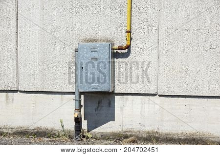 Old water metal pipes fixed with brackets in front of a plaster wall with metal box for water meter