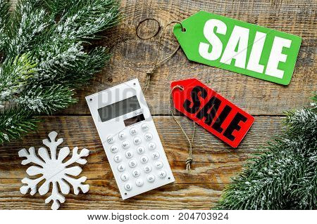 Count the benefits from the winter sale. Word sale on colored labels near calculator and spruce branch on wooden background top view.