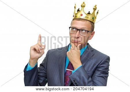 Expert opinion. Judge. Young caucasian business man in suit and glasses and with golden crown above his head keeps his finger on his chin and thinking about business strategy. Career ladder. Success.