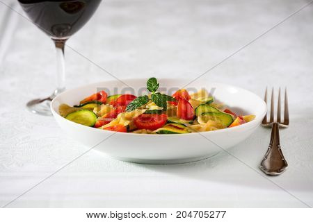 Whole farfalle pasta with zucchini cherry tomatoes and red onion with a red wine glass