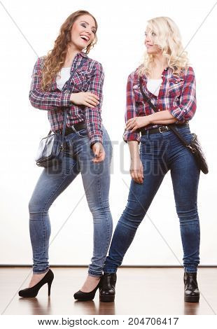 Generation relationship and fashion concept. Adult daughter and mother posing in full length with handbags. Two attractive casual style women wearing denim pants plaid shirts