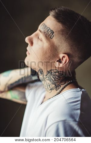 Side view of casual man in white t-shirt showing tattoos on all body while posing outside.