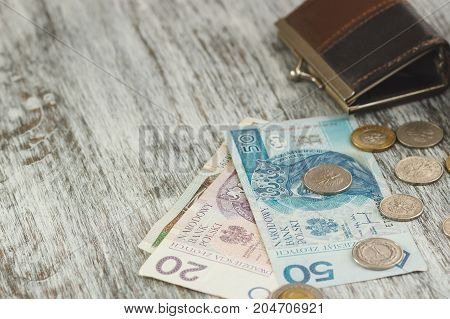 Polish Zloty With Little Wallet On The Old Wooden Background