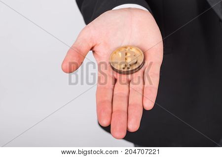 Golden bitcoin on a hand. Crypto currency, virtual money, internet and economics concept.