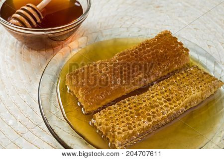 Honey and two honeycombs on natural matting