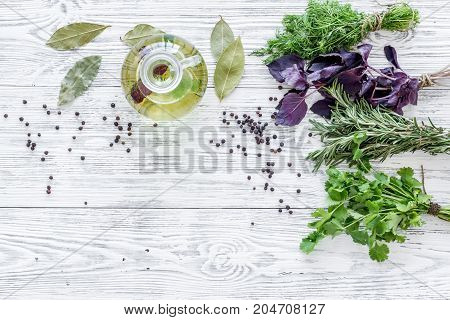 greenery with natural oil for home food cooking on light wooden kitchen table background top view mock-up