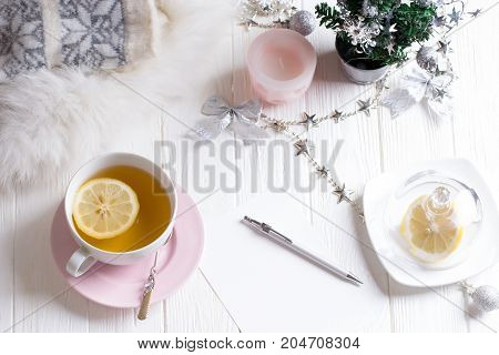 Winter time. Cup of hot tea with lemon. Cozy and soft winter background. Copy space for wishlist or shedule