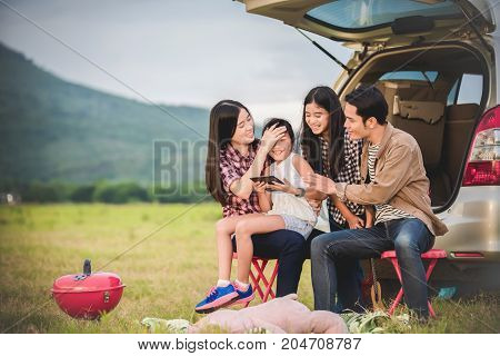Happy little girl with asian family sitting in the car for enjoying road trip and summer vacation in camper van
