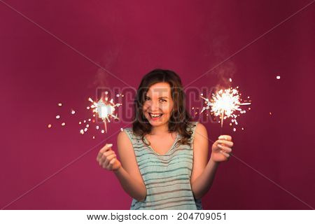 Woman holding sparklers. Christmas, new year and holidays concept.
