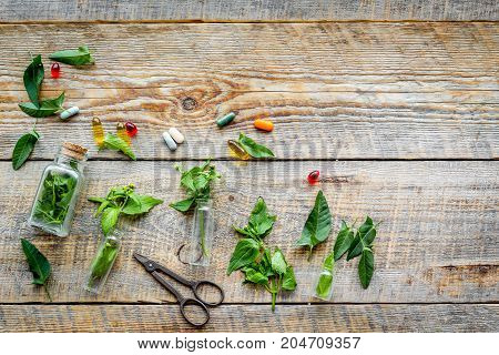 Harvest medicinal herb. Leaves, bottles and sciccors on wooden background top view.