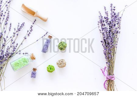home made spa with lavender herbs cosmetic salt for bath on white desk background top view