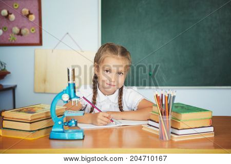Young Child Girl Drawing Or Writing With Colorful Pencils In Notebook In School Over Blackboard