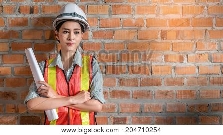 portrait of beautiful woman engineer in front of brick wall with copy space