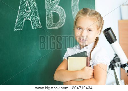 Young Girl Writing Abc On Green Chalkboard