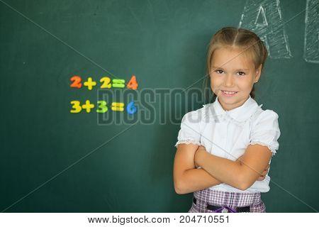 Pretty Schoolgirl Standing Near Blackboard And Smiling