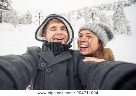people, season, love, technology and leisure concept - happy couple taking selfie by smartphone over winter background.