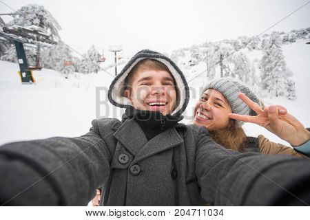 Young man and woman taking a selfie in winter using smart phone