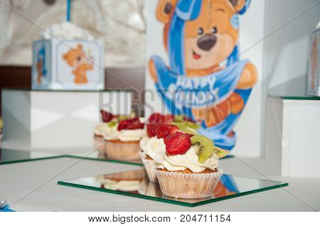 Birthday composition. Three cupcakes with white butter cream and slices of strawberry kiwi on celebration pictures background