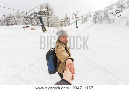 Follow me girl holding boyfriend hand in winter snow nature. Ski resort on the background.