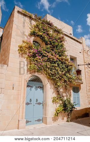 House covered in flowers in Mdina, Malta